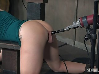 Babe fucked by a machine while sucking an erected prick
